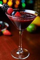 bicchiere di gustoso cocktail tropicale con frutti di bosco o limonata.