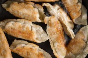 Chiuda sul gnocco fritto alimento asiatico in pentola di cottura foto