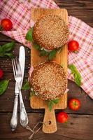 hamburger con pancetta, rucola e pomodoro su fondo di legno rustico foto