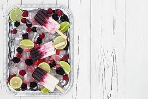 ghiaccioli alla vaniglia di bacche in un vassoio di ghiaccio d'argento vintage