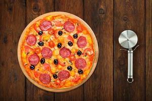 deliziosa pizza con salam e funghi con taglierina in acciaio foto