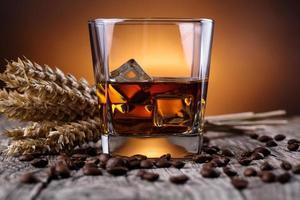 bicchiere di whisky con chicchi di caffè e grano. foto