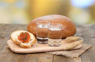 composizione con bicchieri di vodka e caviale rosso sul tavolo