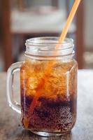 bicchiere di cola con ghiaccio sul tavolo di legno foto