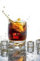 cubetto di ghiaccio lasciato cadere nel bicchiere di cola foto