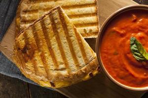 un panino alla griglia con una scodella di zuppa di pomodoro