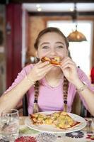 ragazza che mangia prosciutto e pizza di anana foto