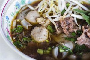 ampia tagliatella di riso in zuppa densa di manzo foto