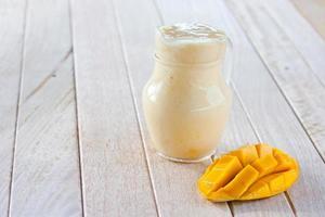frullato di mango sul tavolo di legno foto