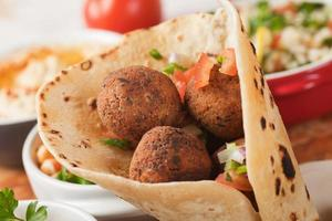 falafel, polpette di ceci fritte nel grasso bollente su pane pita foto