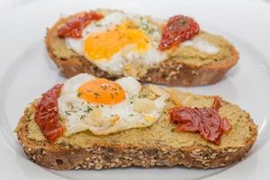 primo piano di tapa spagnola con uovo fritto e pomodoro secco foto