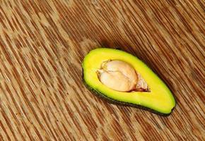frutto di avocado su uno sfondo di legno con focus sul core foto
