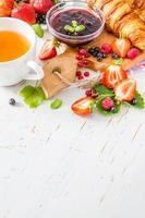 colazione - cornetti con straberry, lampone e mora, tè, marmellata foto