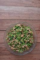 maiale macinato fritto piccante con foglie di basilico