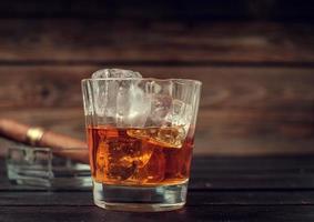 bicchiere di whisky con ghiaccio e sigaro