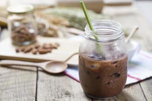 bevanda fredda al latte al cioccolato (primo piano sparato) su fondo di legno foto