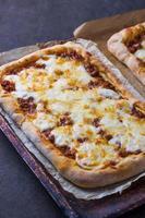 Pizza con carne su una tavola di legno foto