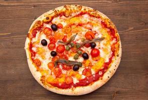 Pizza con acciughe e olive su legno dall'alto foto