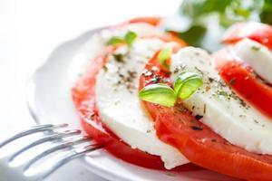insalata caprese, piatto bianco, fondo di legno bianco foto