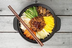 cucina coreana, bibimbap in una pentola di terracotta foto