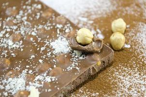 cioccolato integrale su un tavolo spruzzato di cacao foto