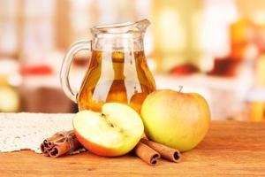 brocca piena di succo di mela sul tavolo su sfondo luminoso