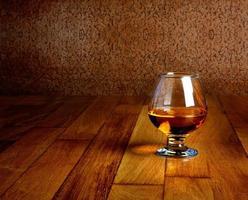 un bicchiere di brandy su ripiano in legno antico