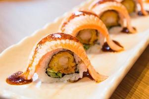 Maki del rotolo di sushi di color salmone fresco crudo - alimento giapponese foto