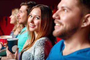 donna con coca cola nel cinema tra lo spettatore foto