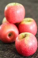 mele rosse su uno sfondo di tessuto marrone foto