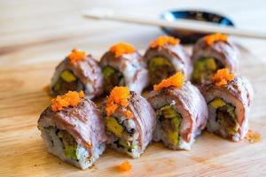 Sushi di rotolo di manzo alla griglia sul piatto di legno foto