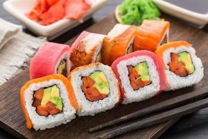 rotolo di sushi arcobaleno con salmone, tonno e anguilla foto