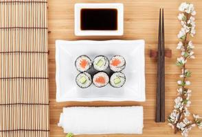 maki sushi con ramo di sakura fresco foto