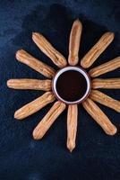 churros fritti con salsa al cioccolato, sole messicano foto
