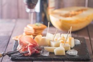 fette di prosciutto crudo con melone e vino rosso foto