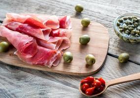 jamon con capperi e olive sulla tavola di legno foto