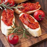 pepe vegetale spalmato sul pane, sul tavolo di legno foto