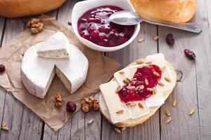 pane servito con camembert e mirtillo rosso. foto