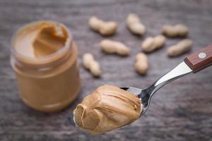 crema di arachidi nel cucchiaio. sullo sfondo. foto