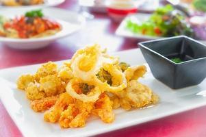 tempura di verdure e bacchette su un piatto bianco. foto