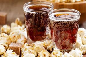 popcorn al caramello e cola in un bicchiere foto