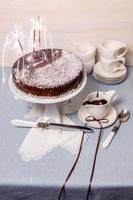 torta festiva con glassa al cioccolato sul tavolo servito stoviglie bianche