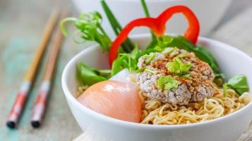 tagliatelle cinesi con carne di maiale tritata e uovo in ciotola foto