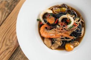 spaghetti frutti di mare piccanti con inchiostro nero foto