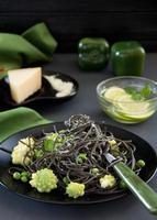 spaghetti al nero di seppia con broccoli e piselli. foto