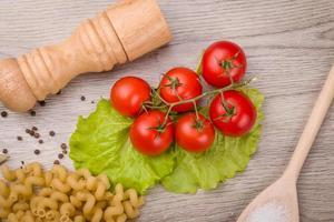 pasta, pomodori e pepe su un fondo di legno