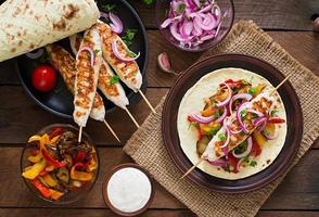 kebab di pollo con verdure grigliate e tortilla. foto