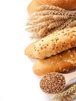 pane, spighe e chicchi di grano su uno sfondo bianco foto