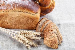 pane di segale, pagnotta di grano con semi di papavero e orecchie. foto