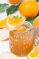 marmellata di arance in un barattolo di vetro e pane fresco, primo piano foto